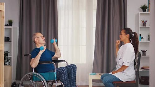 Old Patient in Wheelchair Doing Recovery Exercises
