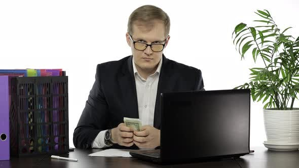 Thumbnail for Businessman Gets and Calculates Money in Office. Hide Paper Banknotes in Pocket