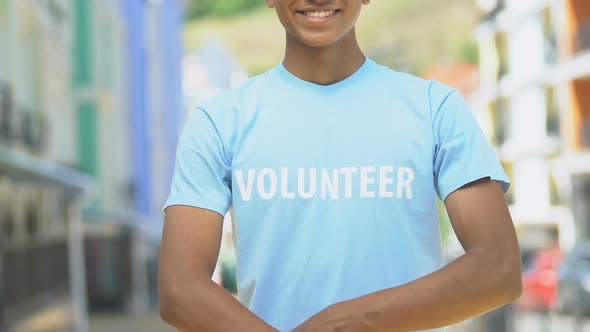 Thumbnail for Volunteer in shirt folding arms smiling outdoors