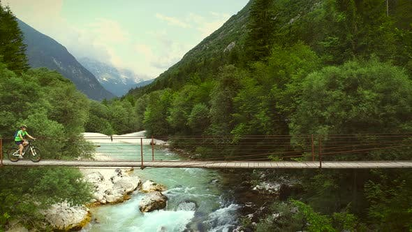 Thumbnail for Aerial view of a woman crossing a wooden bridge on a mountain bicycle.