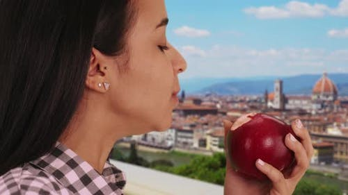 Latina enjoys a savory apple on a warm day in Florence