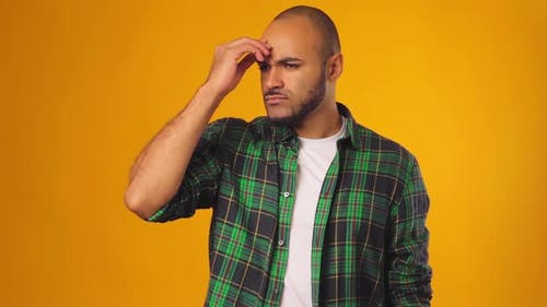 Pensive African American Man Touching His Forehead and Thinking Against Yellow Background