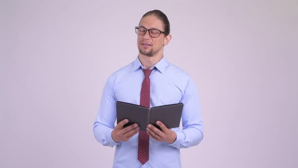 Thumbnail for Happy Handsome Businessman Reading Book with Eyeglasses and Thinking