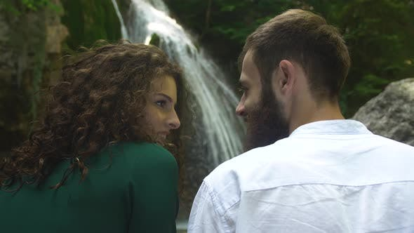 Thumbnail for Young and Beautiful Man and Woman Look at Each Other Against the Backdrop of a Waterfall in a