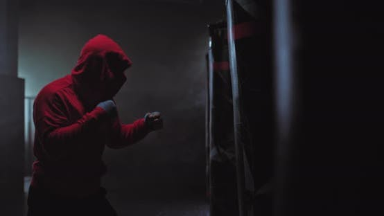 Portrait Silhouette of a Male Boxer in a Hood in a Dark Sports Hall Tubers of Smoke