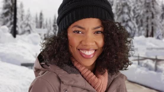 Thumbnail for Close up of cute black female outdoors in snow smiling at camera
