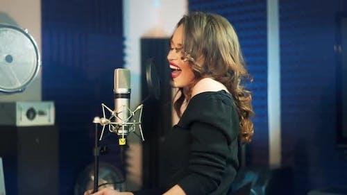 Mädchen singt am Mikrofon in einem Studio. Weiblicher Gesang.