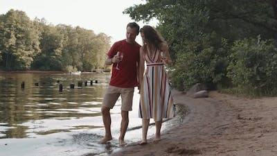 Couple Walking by Pond Shore