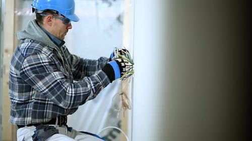 Man in Mid 30s Separates Wires In New Electric Outlet.