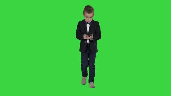 Thumbnail for Small Boy in Costume Walking and Using Smartphone on a Green Screen