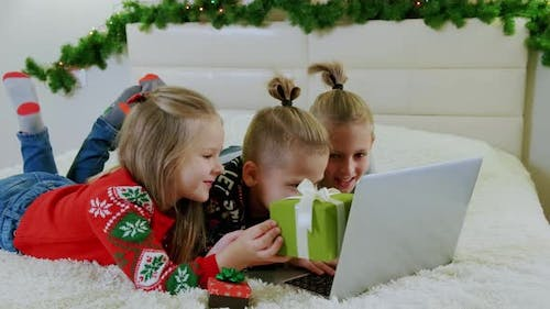 New Year's Concept Children Lie Couch Christmas Clothes Make Online Call Laptop