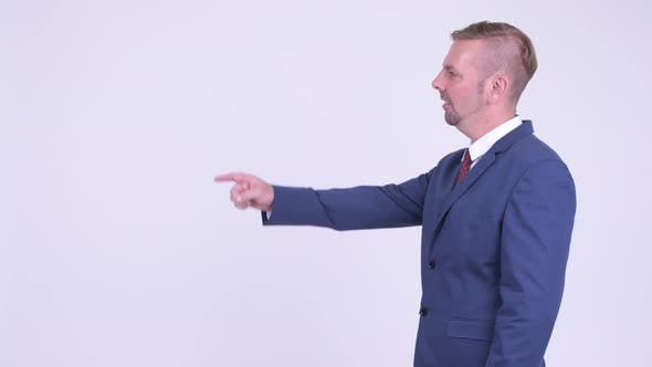 Thumbnail for Profile View of Happy Blonde Businessman Pointing Finger