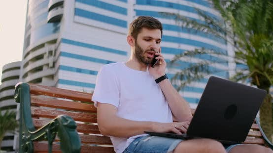 Thumbnail for Young Man Sitting in the Park with Palm Trees and Laptop Talking on the Phone