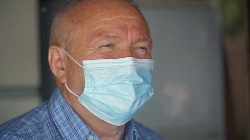 Mann in Gesichtsmaske hinter dem Fenster