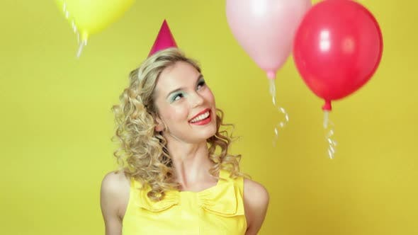 Thumbnail for Young woman in party hat and floating balloons