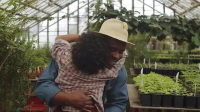 Afro-American Dad Bonding with Son in Greenhouse