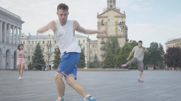 Thumbnail for Wide Shot of Confident Man Performing Break Dance with Friends Dancing at the Background. Group of