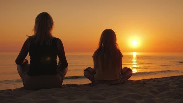 Thumbnail for A Woman with Her Daughter Sitting Side By Side on the Sand in a Lotus Pose