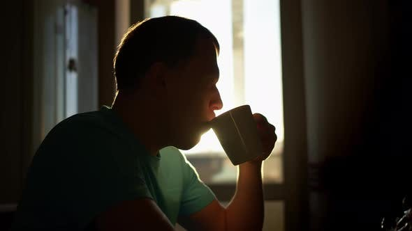 Silhouette of a young man in the sunbeams of dawn drinks hot coffee while sitting at home
