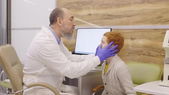 Thumbnail for Elderly Ophthalmologist Examining Eyes of Little Boy