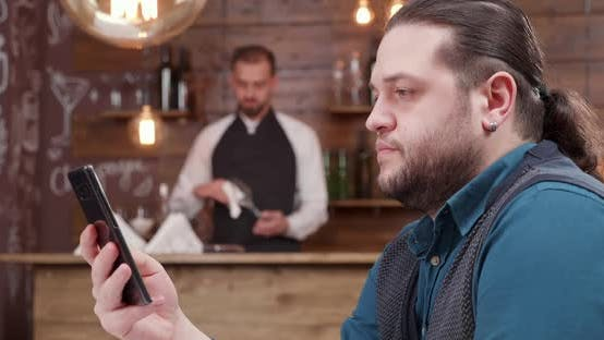 Thumbnail for Man Looking at His Phone Screen a Bit Concerned