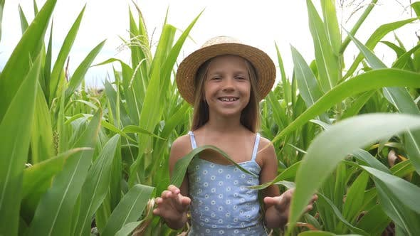 Thumbnail for Close Up of Beautiful Cute Girl in Straw Hat Going To the Camera Through Corn Field. Happy Small Kid