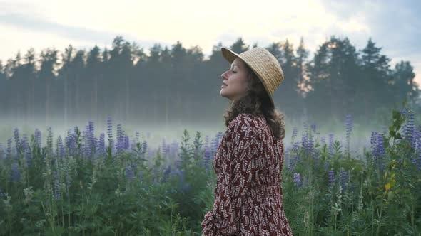 Thumbnail for Happy Romantic Girl in einem Kleid und Hut Spaziergänge entlang des Feldes mit Blumen und Nebel, Tänze inspiriert
