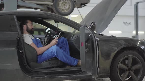 Thumbnail for Successful Mechanic Sitting Inside the Car and Verifies Information on His Phone