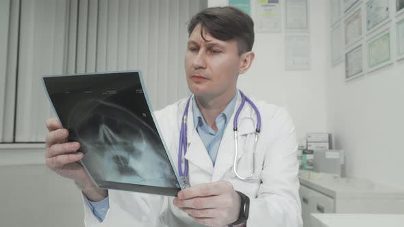 Mature Male Doctor Examining Head MRI Scan of His Patient