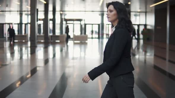 Thumbnail for a Young Woman in a Business Suit Walks Through the Lobby of a Modern Office Building.