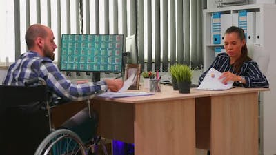 Businessman in Wheelchair Working in Corporate Office
