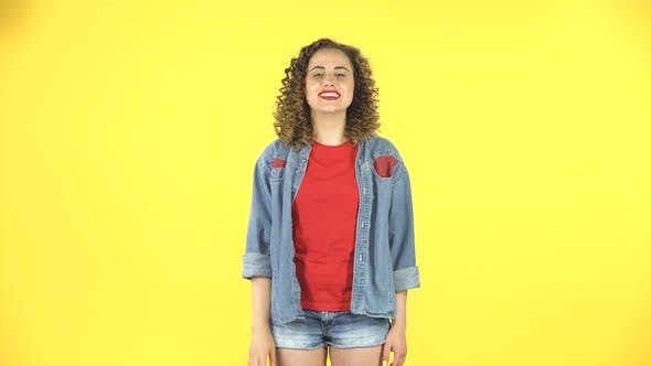 Thumbnail for Young Curly Girl Shows Two Fingers Victory Gesture on Yellow Background at Studio