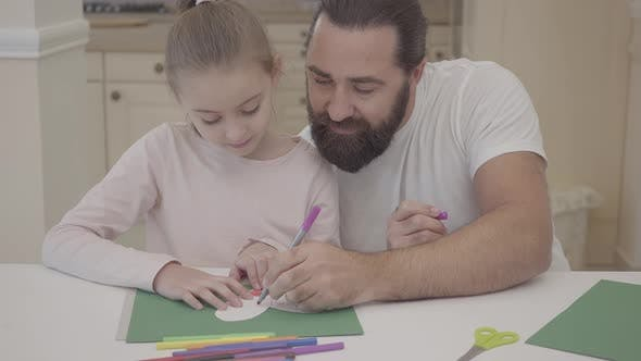 Thumbnail for Young Father and His Small Cute Daughter Are Sitting in Living Room and Drawing with Markers