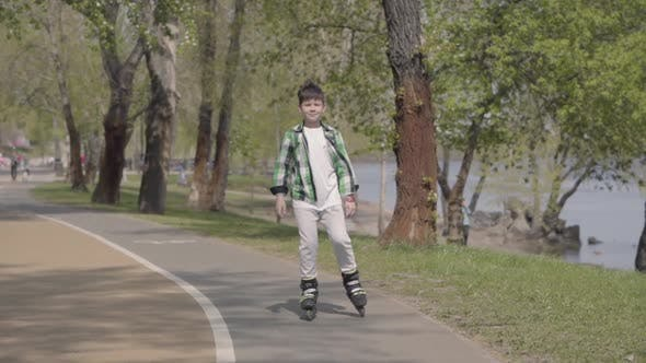 Cover Image for Cute Boy in Bright Clothes Rollerblading in the Park Near the River