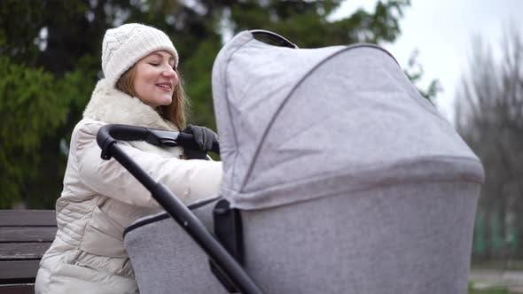 Thumbnail for Junge Mutter mit neugeborenem Kind im Freien. Sie sitzt auf der Bank mit Baby schlafen im Kinderwagen