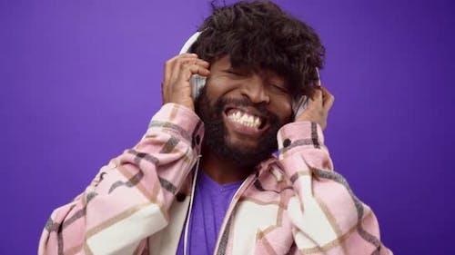 Joyful Smiling African American Man Listening to Music in Headphones Against Purple Background