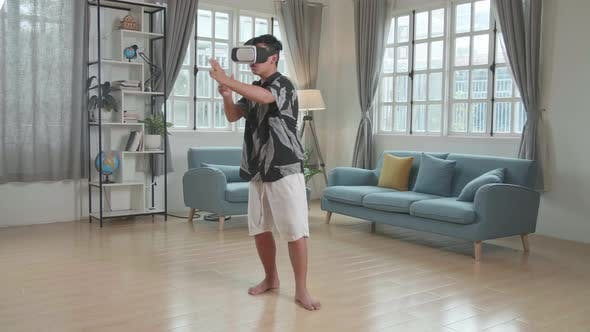 Boy Playing Video Game While Wearing VR Glasses Headset At Living Room