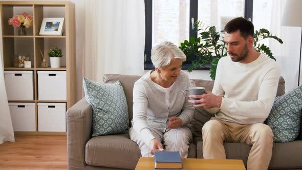 Cover Image for Adult Son Bringing Coffee To Senior Mother at Home