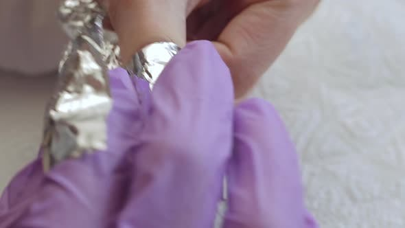Thumbnail for A Young Woman Does a Manicure. Wraps His Fingers in Foil To Remove the Old Gel. Nails Manicure