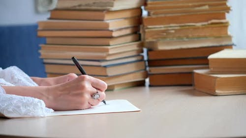 Woman writing letter on a piece of white paper. Closeup of female hands write notes
