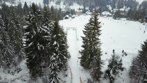 Flight Over a Ski Resort in Carpathian Mountains. Aerial View of People Descending on Skis