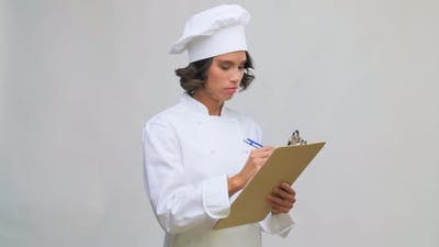 Female Chef in Toque with Pen Writing To Clipboard