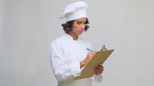 Chefkoch in Toque mit Kugelschreiber zum Klemmbrett