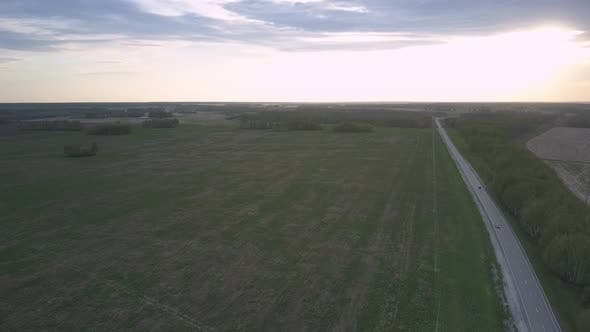Thumbnail for Wide Green Unharvested Field and Long Highway Against Forest