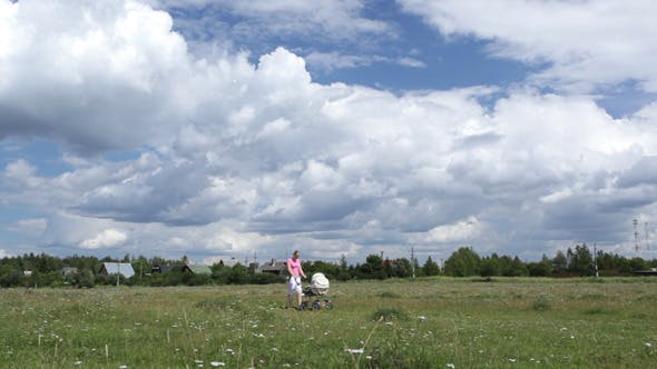 Thumbnail for Young Mother Walking In The Field With Buggy