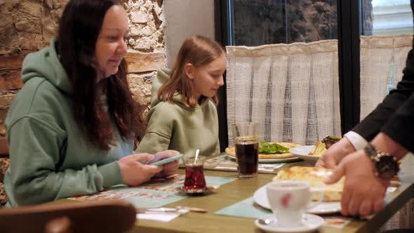 Waiter Bringing Pizza and Pie for Family in Restaurant