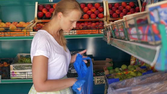 Cover Image for Young Woman Choosing Pears in Fruit Shop