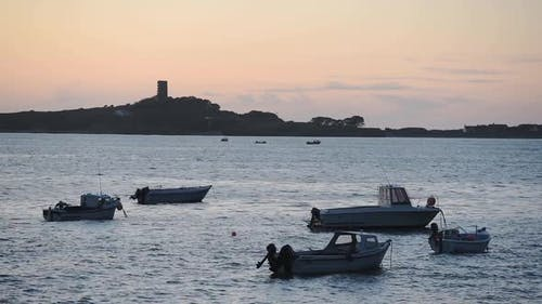 Small Fishing Boats Anchored On The Calm Ocean In St. Peter Port, Guernsey, Channel Islands, UK Duri