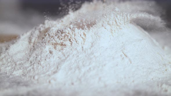 Extreme close up of egg falling into flour