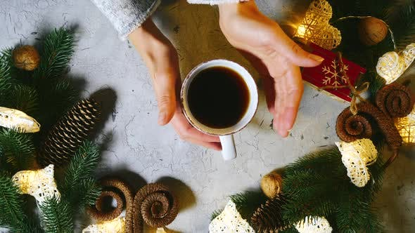 Cup of Warm Black Tea or Coffe on a Table Among Christmas Decorations. Girls Hand Slowly Picks Up It